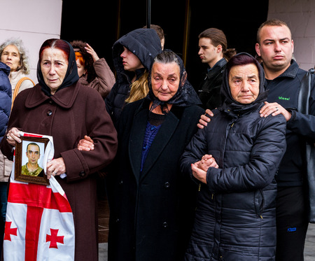 Uzhhorod, Ukraine - 2016. October 12: Relatives of ukrainian soldier who died of his wounds in the ATO zone, kept a portrait and the Georgian flag during a farewell ceremony. The coffin with the body of the deceased Ukrainian heroic warrior honorably carr