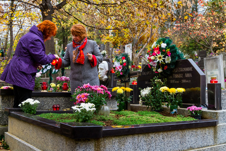 Uzhgorod, Ukraine - November 1, 2016: Women set fire to candles in memory of deceased relatives graves on the Day of All Saints. On this day, the locals decorate the graves with flowers and burning candles of memory. Editorial