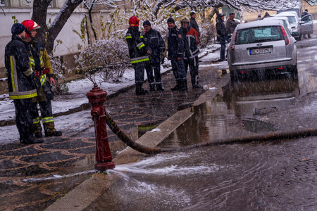 fire extinguishing: Uzhgorod, Ukraine - December 1, 2016: Firefighters stand near flowing worthless old hydrant during fire extinguishing on a city street. Editorial