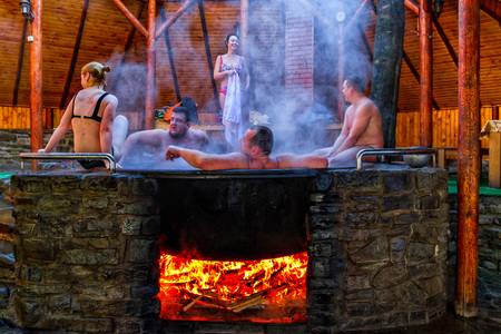 Lumshory, Ukraine - January 10, 2017: Tourists bathing in the cast iron vat with mineral water containing hydrogen sulphide. Water in cast iron vats heated to 40-45 degrees Celsius. Редакционное