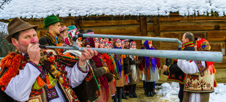 Uzhgorod, Ukraine - January 15, 2017: Member of folklore band plays on trembita during the seventh ethnic festival Christmas Carols in the old village. During the festival, visitors can familiarize with a variety of Christmas customs, caroling and celebra