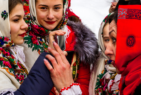 nationality: Uzhgorod, Ukraine - January 15, 2017: Members of folklore groups use the mobile phone as a mirror during the seventh ethnic festival Christmas Carols in the old village. During the festival, visitors can familiarize with a variety of Christmas customs, ca