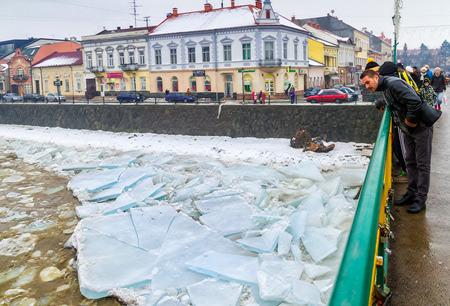 cloud drift: Uzhgorod, Ukraine - February 3, 2017: A man from the bridge watching the ice drift on the river.