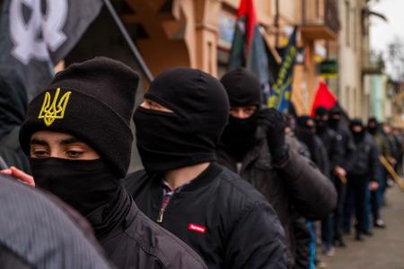 partake: Uzhhorod, western Ukraine -  March 18, 2017: Masked activists partake in the Black March of the Glory of the Heroes of Carpathian Ukraine in Uzhhorod.