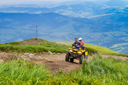 Pylypets, Ukraine - June 25, 2017: Tourists on a quad bike climb to the peak of Mount Hymba in the Carpathians near the village of Pylypets.