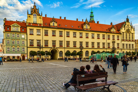 Wroclaw, Silesia, Poland - July 25, 2017: Tourists relax on a bench in the market square in the historic part of the city.