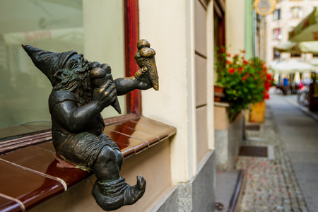 Wroclaw, Silesia, Poland - July 25, 2017: Miniature bronze figure of a gnome who eats ice cream on the windowsill of an old confectionery in the city center.