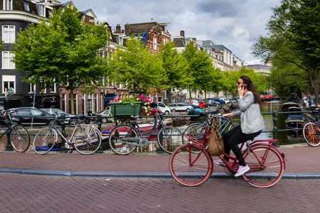 AMSTERDAM, NETHERLANDS - 27 JULY 2017: Unknown girl rides a bicycle on a bridge in Amsterdam.