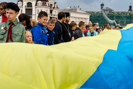 Uzhgorod, Ukraine - August 23, 2017: Local schoolchildren and priests carry a 100-meter flag during the celebration of the National Flag Day of Ukraine, in Uzhgorod. Editorial