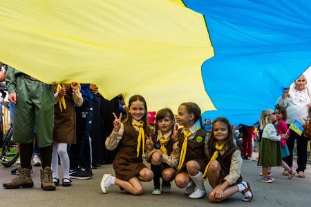 Uzhgorod, Ukraine - August 23, 2017: Little girls scouts sit under the 100-meter flag during the celebration of the Day of the State Flag of Ukraine, in Uzhgorod.