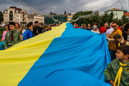 Uzhgorod, Ukraine - August 23, 2017: Townspeople and small scouts carry a 100-meter flag during the celebration of the Day of the State Flag of Ukraine, in Uzhgorod. Editorial