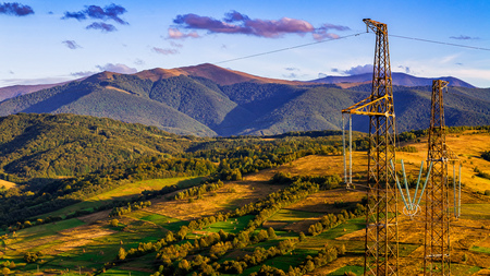 High voltage lines and and power pylons against the background of a beautiful autumn landscape in the Carpathian Mountains. Stock Photo