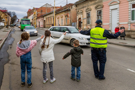 Children help the policeman to regulate the traffic on one of the streets of the city.