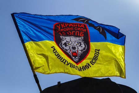 Flag of the reconnaissance platoon of the 15th separate mountain infantry battalion against the blue sky.