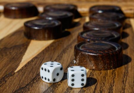 Wooden Backgammon game board with cubes and dices.
