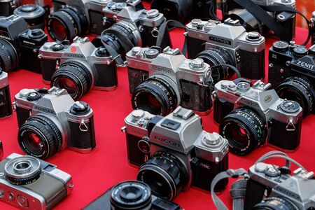 Vintage film cameras for sale on a red canvas background at a flea market in Lisbon, Portugal, January 7, 2020. 版權商用圖片 - 140652289