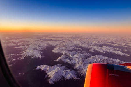 Beautiful sunset over the snowy Alps. View from the porthole of an airplane.