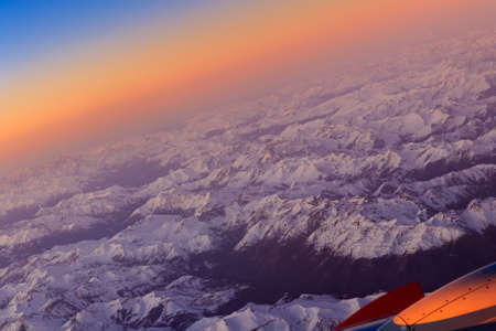 Beautiful sunset over the snowy Alps. View from the porthole of an airplane. The plane lowers the height.