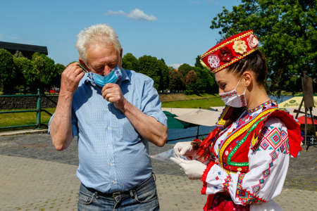 Uzhgorod, Ukraine - May 21, 2020. A girl in Ukrainian national costume gives passers-by protective masks with embroidery during an art mob on the occasion of Embroidered Shirt Day.