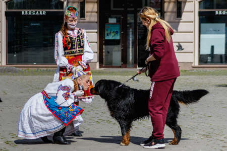 Uzhgorod, Ukraine - May 21, 2020. A girl in a Ukrainian national costume kisses a dog during an art mob on the occasion of Embroidered Shirt Day.