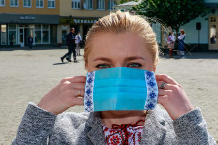 Uzhgorod, Ukraine - May 21, 2020. A girl in a Ukrainian embroidered shirt wears a protective mask with embroidery during an art mob on the occasion of Embroidered Shirt Day.