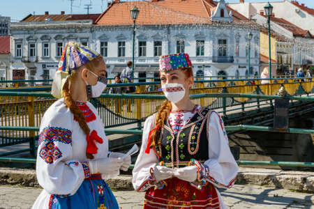 Uzhgorod, Ukraine - May 21, 2020: Girls in Ukrainian national costumes and embroidered protective masks talk during an art mob on the occasion of Embroidered Shirt Day.