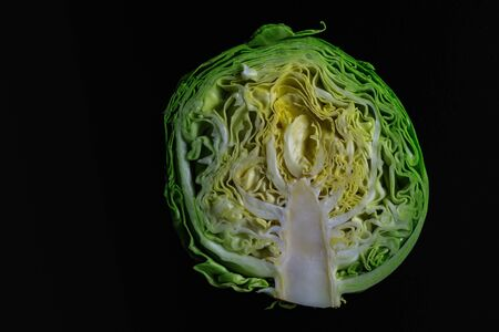 Half fresh young cabbage on a dark background in natural light. Banque d'images