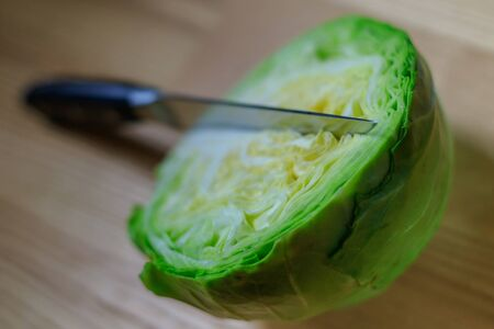 Half fresh green cabbage on a wooden board with a kitchen knife in natural light. Soft image with selective focus.
