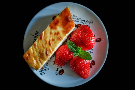 Piece of homemade cheesecake on a plate decorated with fresh strawberries and mint leaves on a black background. Top view. Close-up.