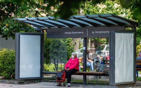 Uzhgorod, Ukraine - June 3, 2020: Elderly woman in a protective mask waiting for a bus at the bus stop. COVID-19 disease protection.