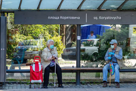 Uzhgorod, Ukraine - June 3, 2020: Elderly people in protective masks/gloves are talking while sitting on a bench at a bus stop observing the rules of social distancing. COVID-19 disease protection.