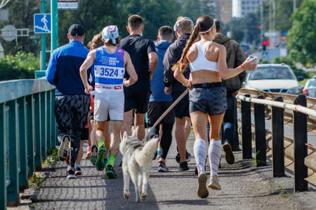 Uzhgorod, Ukraine - June 7, 2020: A group of young people run across the bridge while relaxing quarantine in Ukraine. Participants in a running event ran a distance of 10 km. Éditoriale