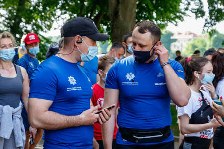 Uzhgorod, Ukraine - June 7, 2020: Police officers in medical masks talk before the start of the running event during the weakening of quarantine in Ukraine. Participants in a running event ran a distance of 10 km. Éditoriale
