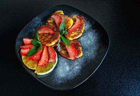Tasty cheese pancakes with slices of orange and strawberries decorated with fresh mint and icing sugar on a black plate. Top view. Close-up.
