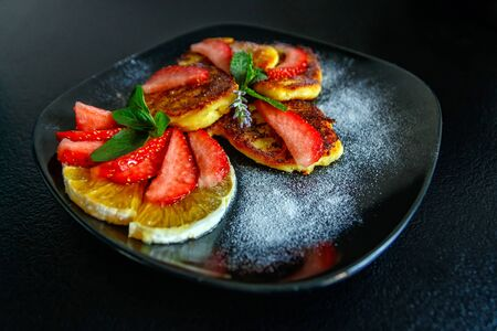 Tasty cheese pancakes with slices of orange and strawberries decorated with fresh mint and icing sugar on a black plate. Close-up.