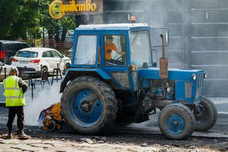 Uzhgorod, western Ukraine - June 11, 2020: Employees of municipal services, repair pavement in the city center during the quarantine due to coronavirus.