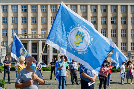 Uzhgorod, Western Ukraine - June 30, 2020: People in protective masks hold flags of trade unions of Ukraine during a protest against anti-professional bill No. 2681 during quarantine.