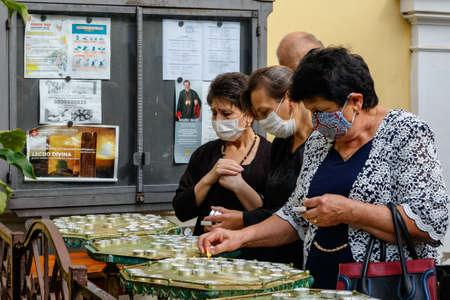 Uzhgorod, Ukraine - July 20, 2020: Women in protective masks light candles during the farewell ceremony with Bishop of Mukachevo Greek Catholic Diocese Milan Shashik.