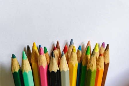 Colored pencils on a light background, selective focus.