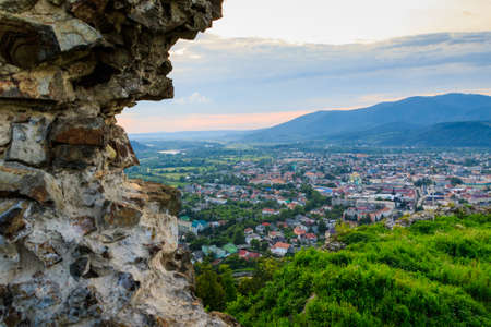 Ruins of old hungarian castle with a city view at sunset, Khust, western Ukraine.