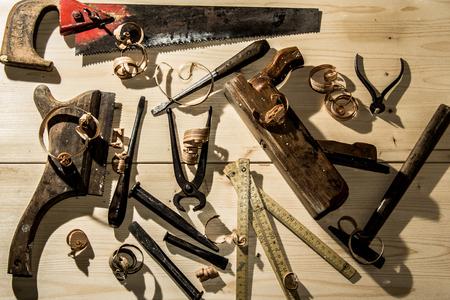 old woodworks tools: wooden planer, hammer, chisel in a carpentry workshop on wood background Standard-Bild