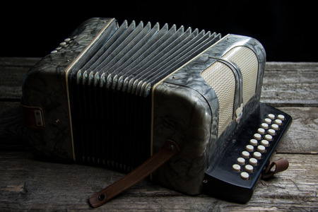 Old accordion on rustic wood table with wine Stock Photo