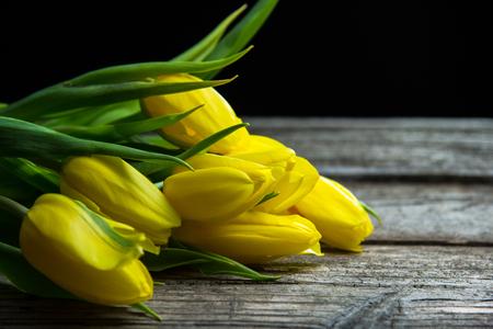 Yellow tulips on rustic old wood table