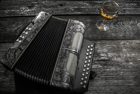 Old accordion on rustic wood table with wine Standard-Bild