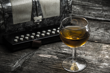 concertina: Old accordion on rustic wood table with wine Stock Photo