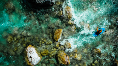 Whitewater rafting on the Emerald waters of Soca River, Slovenia, are the rafting paradise for adrenaline seekers and also nature lovers, aerial view.