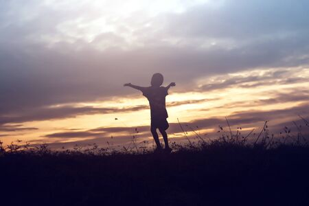 Silhouette of kid and the beautiful sky in the evening Stock Photo