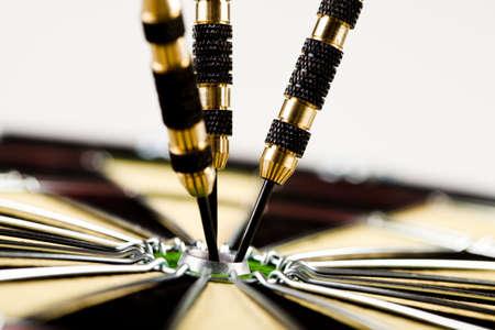 ide: Cut image of dart pierced on target over dartboard