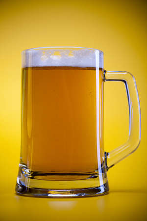 Beer glass with yellow background  photo