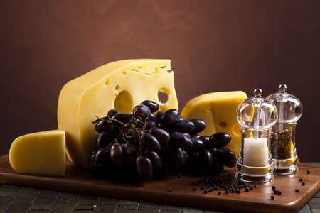 tabla de quesos: Quesos con uvas Foto de archivo